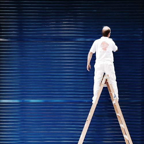 Rear View Of Person Painting Shutter While Standing On Ladder