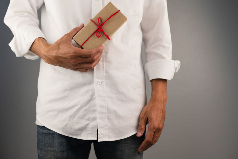 Midsection of man holding hands against white background