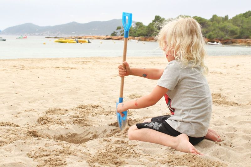 Side View Of Boy Playing In Sand At Beach