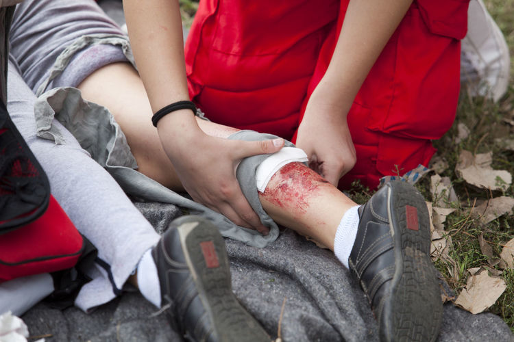 Low section of paramedic sitting by wounded woman on field