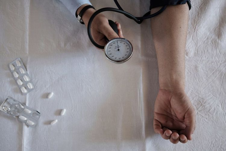 Cropped hand of doctor examining patient blood pressure by pills on bed at hospital