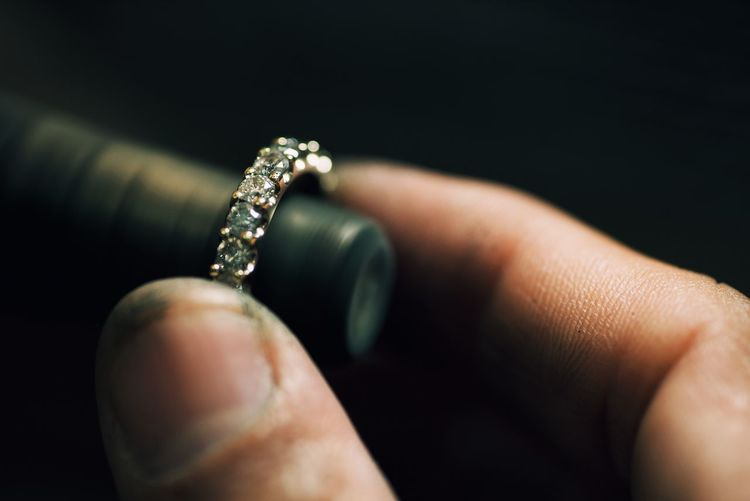 Close-up of hand making ring over black background