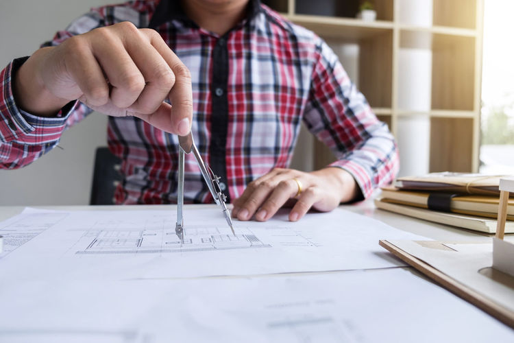 Midsection of architect drawing blueprint on paper in office