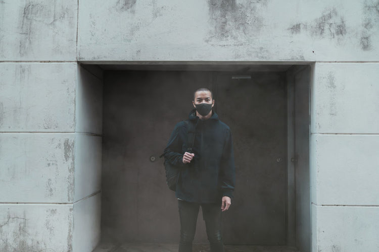 Man standing against wall in city