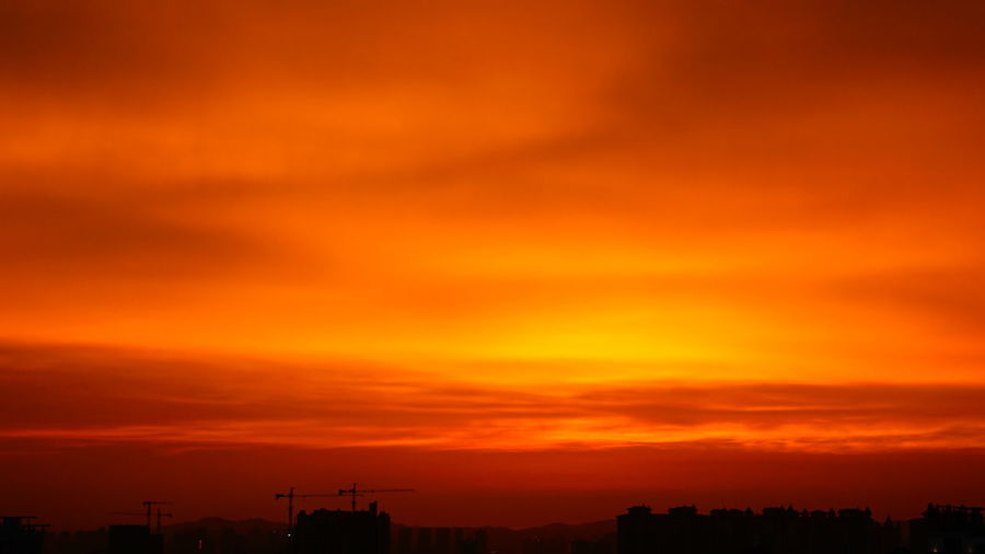 Low angle view of silhouette buildings against orange sky