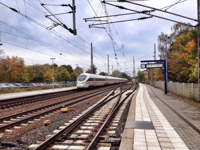 Speeding train at railway station against the sky