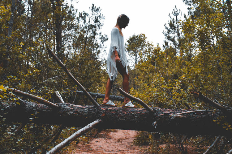 Side View Of Young Woman Walking On Fallen Tree In Forest