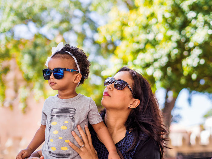 Mother And Daughter Wearing Sunglasses Against Trees At Park