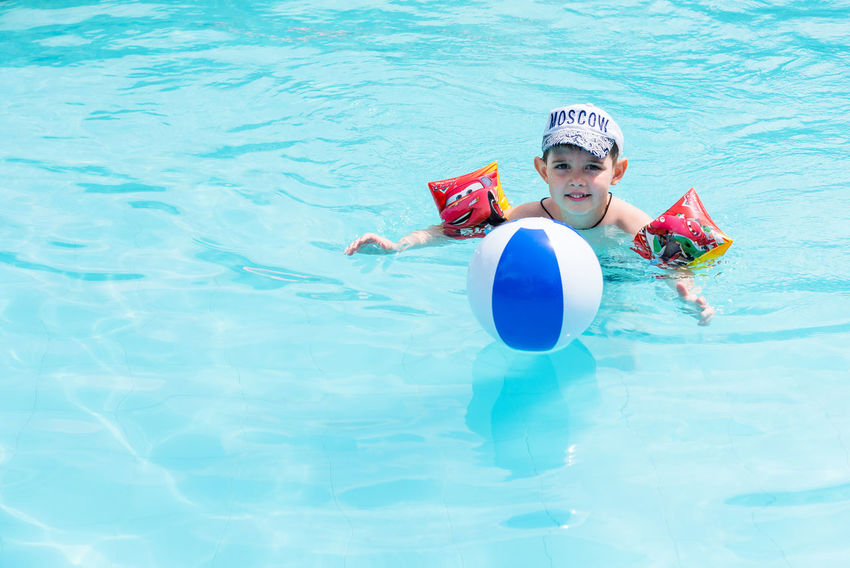 Trat, Thailand - May, 21, 2017 : Unidentified name Boys swimsuit floating and playing with ball in the swimming pool at Klong Prao Resort in Prao Beach Koh Chang island Trat, Thailand. Childhood Day Editorial  Happiness Headwear Illustrative Illustrative Editorial Inflatable Ring Leisure Activity Lifestyles Looking At Camera Nature One Person Outdoors People Portrait Real People Smiling Swimming Swimming Goggles Swimming Pool Thailand Water
