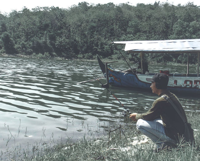 Rear view of man sitting on boat in lake