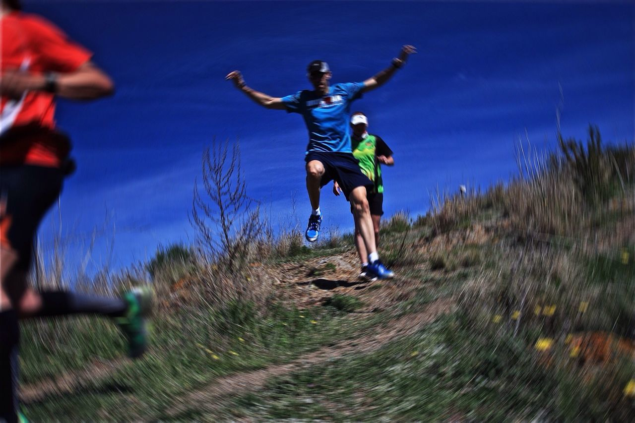 motion, running, full length, outdoors, mid-air, speed, real people, day, jumping, lifestyles, exercising, blue, sports clothing, sport, men, sky, one person, grass, athlete, nature, young adult, adult, people