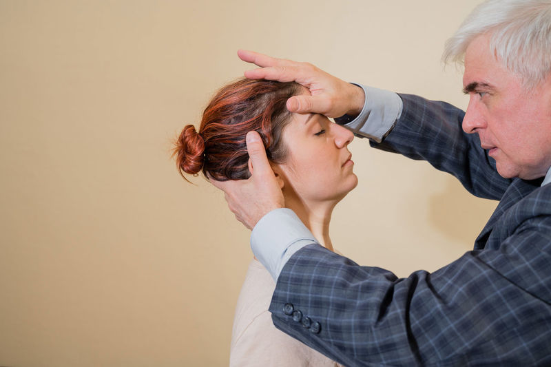 Portrait of man treating female patient against wall