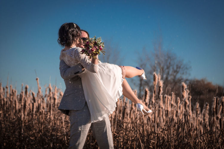 Groom carrying bride holding bouquet on land against sky