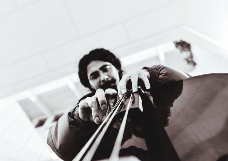 Low angle view portrait of young man playing musical instrument