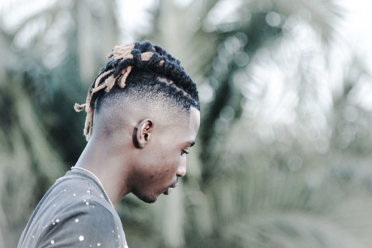 Close-up of man with hairstyle looking away
