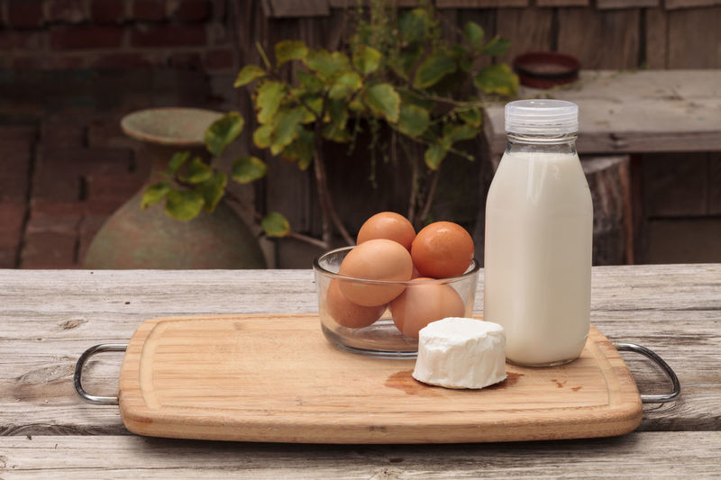 Fresh organic brown eggs in a clear glass bowl, glass bottle of milk, and goat cheese on a rustic farm picnic table in summer. Cheese Chicken Egg Close-up Dairy Dairy Farm Eggs Farm Farm To Table Fresh Freshness Glass Bowl Goat Cheese Milk Natural No People Organic Picnic Table Rustic Wood - Material Wood Table