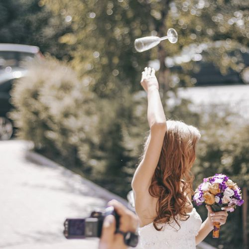 Cropped hand of man filming bride throwing champagne flute against plants