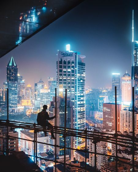Rear View Of Silhouette Man Sitting Against Illuminated Buildings On Construction Site In City At Night