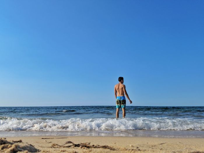 Rear view of shirtless man standing on shore at beach against clear sky