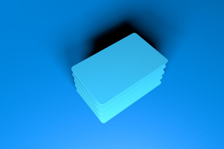 High angle view of cards against blue background