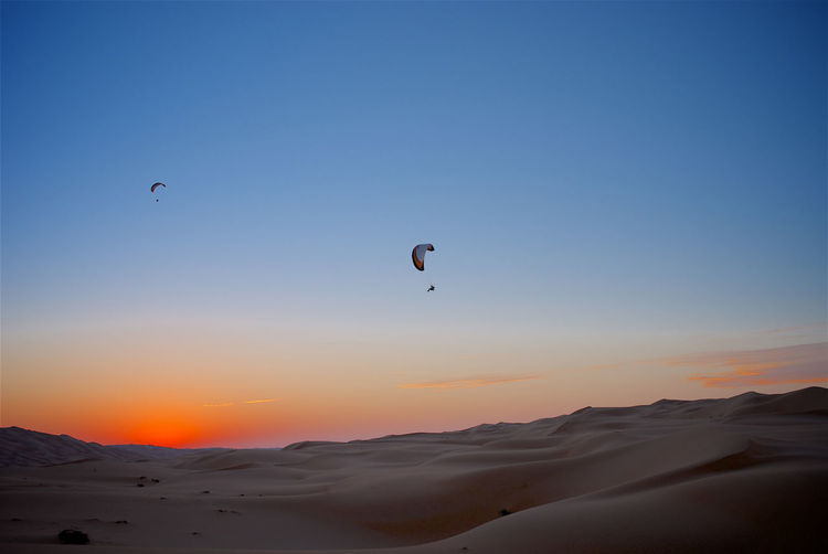 Desert Empty Quarter Adventure Beauty In Nature Clear Sky Extreme Sports Flying Land Leisure Activity Mid-air Nature Non-urban Scene Parachute Paragliding Scenics - Nature Sky Sport Sunset Tranquil Scene Tranquility Unrecognizable Person