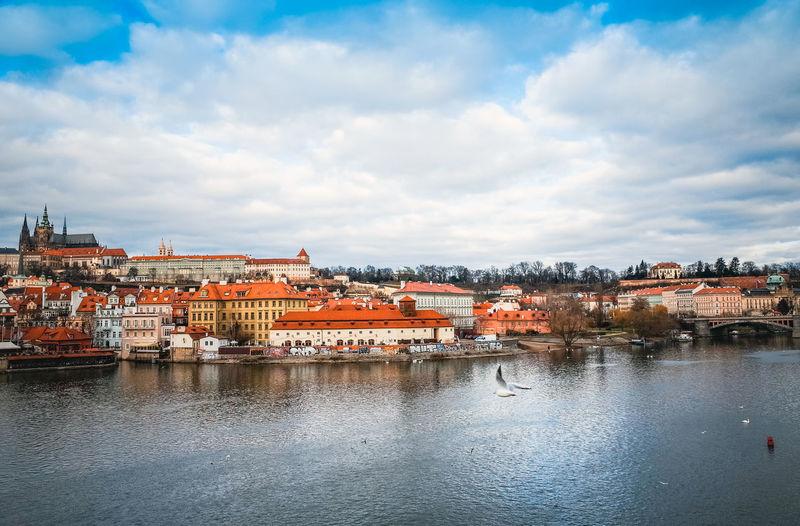 Vltava river by city against cloudy sky