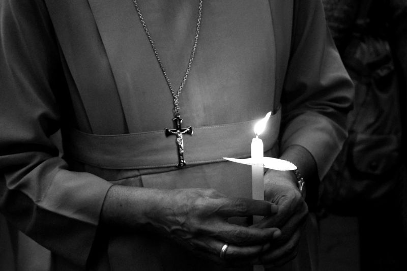 Midsection of nun holding lit candle in dark