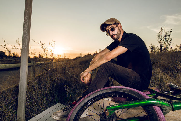 Portrait Of Man Sitting With Bicycle On Field Against Sky During Sunset
