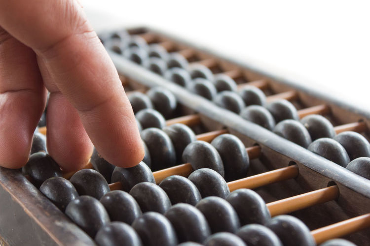 Cropped hand playing with abacus against white background