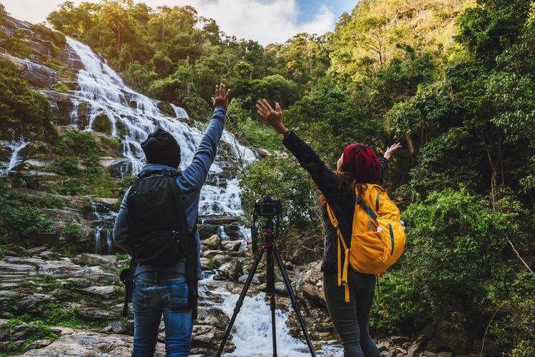 Rear view of friends with arms raised standing by waterfall and camera in forest