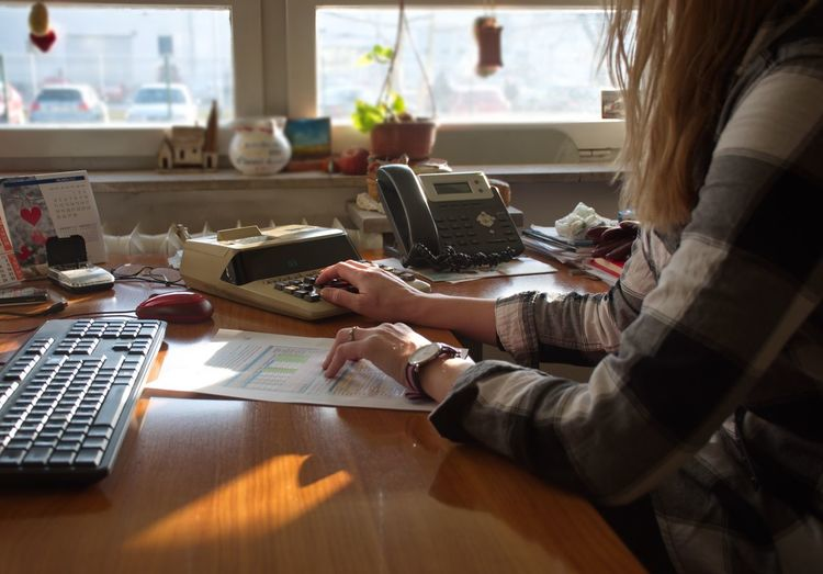 Midsection of woman using calculator in office