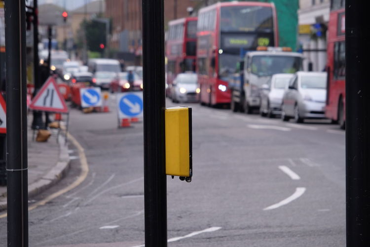 Pedestrian push button on pole against road in city