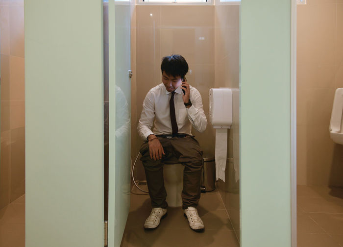 An Asian business man pooping and phoning in bathroom, person Busy Day Front View Full Length Indoors  Lifestyles Mobile Phone One Person People Phone Pooping Real People Standing Talking Technology Using Phone Wireless Technology Young Adult