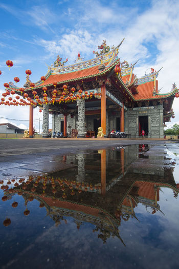 Benoa, Bali, Indonesia - January 28, 2017 : People praying and wishing a happy chinese new year on vihara satya dharma. Architectural Column Architecture Belief Building Building Exterior Built Structure Cloud - Sky Day Lake Nature No People Ornate Outdoors Place Of Worship Reflection Religion Sky Spirituality Travel Destinations Water Waterfront