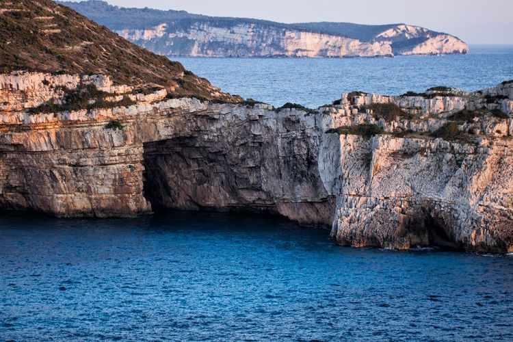 Caves at the Paxos island, south of Corfu, in Greece. Water Sea Rock Rock - Object Scenics - Nature Solid Cliff Beauty In Nature Rock Formation Nature Tranquil Scene No People Tranquility Land Day Outdoors Waterfront Travel Destinations Rocky Coastline View Into Land Eroded Cave