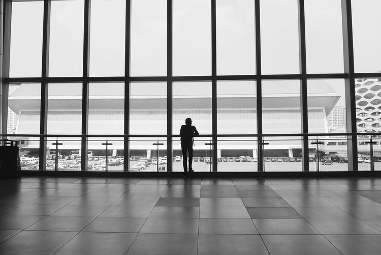 Man at airport against sky seen through window