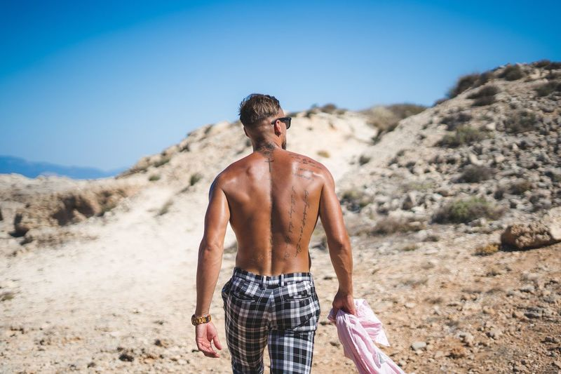 Rear view of shirtless man standing on land against sky