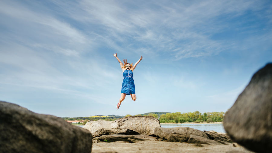 Rear view of man jumping on rock against sky