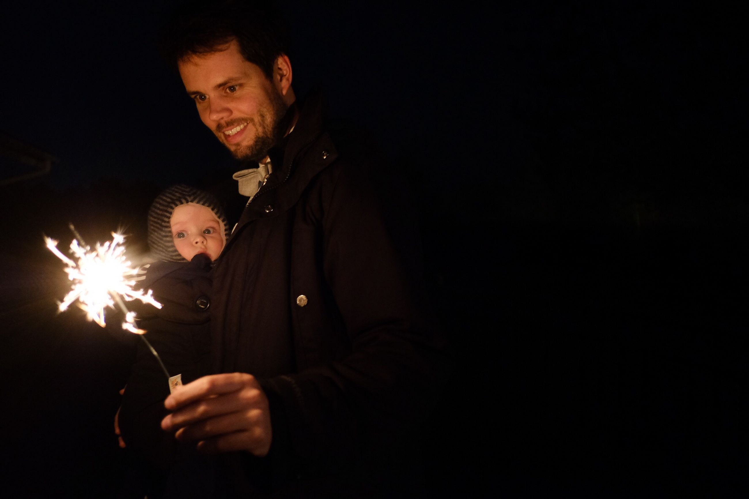 men, illuminated, glowing, night, males, two people, sparkler, burning, holding, celebration, mid adult men, lifestyles, real people, mid adult, copy space, portrait, dark, young adult, leisure activity, black background, sparks, firework