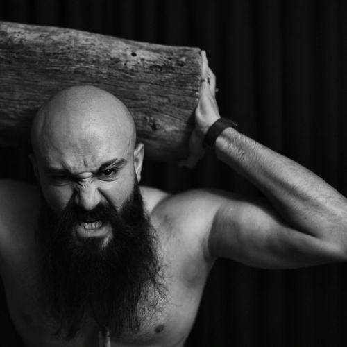 Portrait Of Shirtless Man Holding Wood Over Black Background
