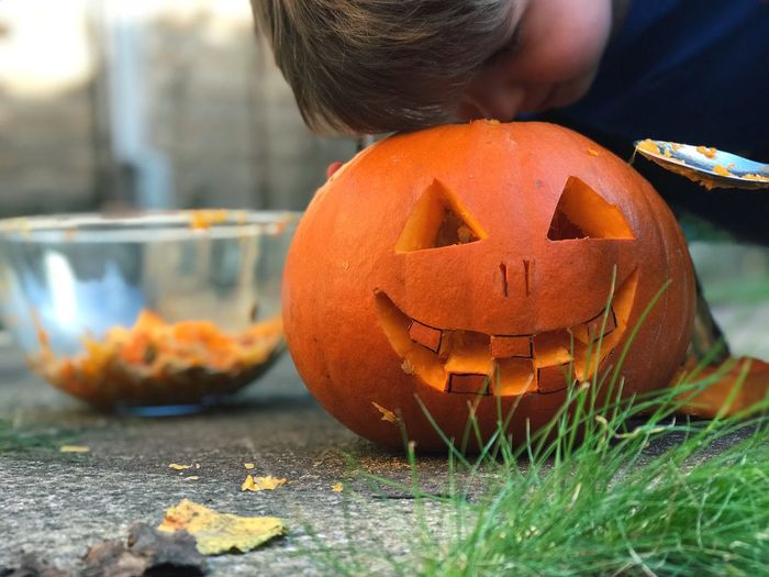 Quality check. Halloween Pumpkin Orange Color Jack O Lantern Focus On Foreground Autumn Outdoors Day Holiday - Event Jack O' Lantern Close-up One Person Real People Childhood People IPhone 7 Plus Second Acts Child ShotOnIphone IPhoneography IPhone Boys Vegetable Lifestyles Tradition