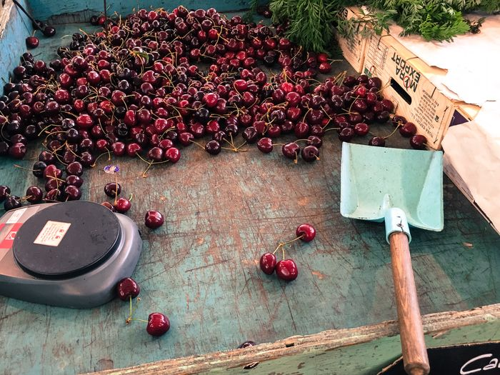High angle view of weight scale and shovel by cherries