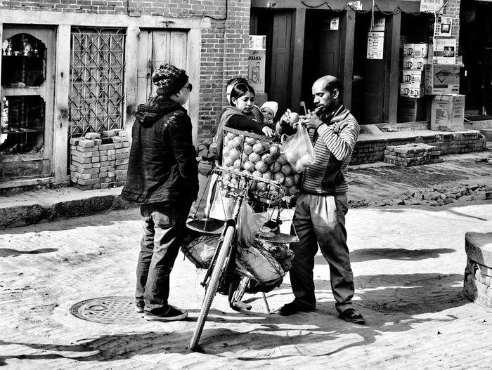 Rear view of people walking on street against building