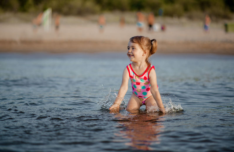 Cute Girl Playing In Sea At Beach