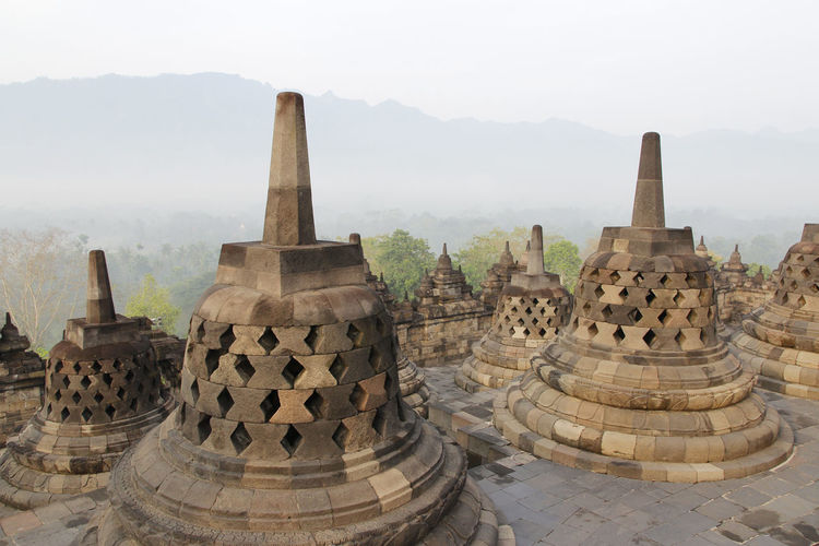 Borobudur Temple with the mysteries forest surrounding during sunrise, Yogyakarta, Indonesia Yogyakarta Ancient Ancient Civilization Architecture Architecture And Art Belief Borobudur Buddhist Temple Building Exterior Built Structure Carving Fog Forest History Nature No People Place Of Worship Religion Spirituality Stone Material Sunrise The Past Tourism Travel Travel Destinations