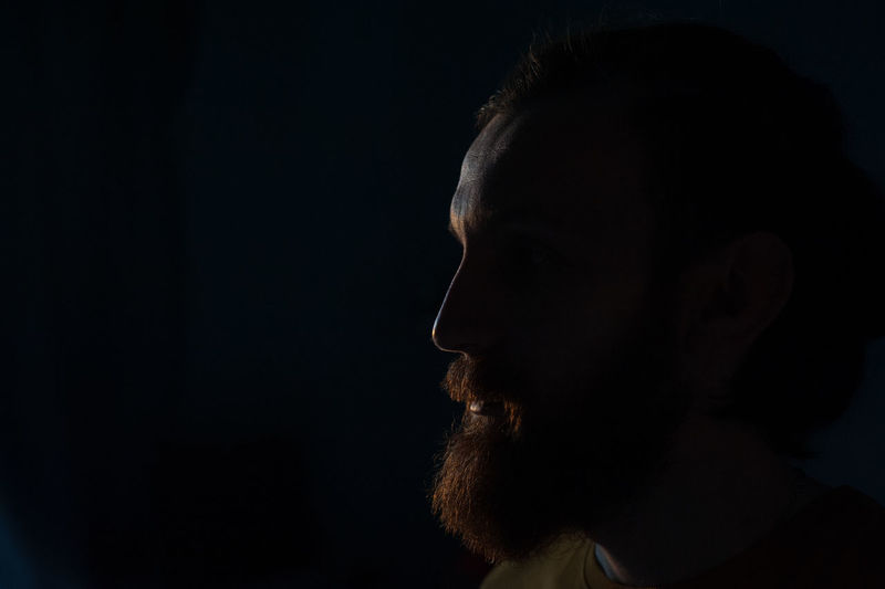 Close-Up Of Man With Beard Against Black Background