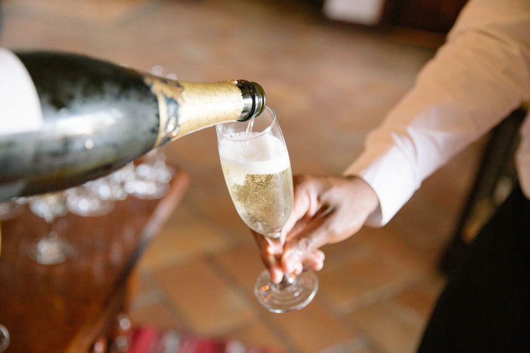 Cropped Image Of Hand Pouring Champagne In Glass