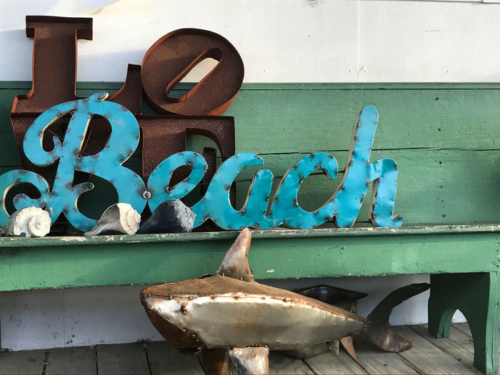 metal sculptures from Ocracoke, NC Bench Blue Color Love Quiet Rustic Alphabet Beach Beach Sign Communication Metal Art Metal Sign Nature No People Ocracoke Island Rustic Beauty Rustic Style Rustic_wonders Rusty Selective Color Serene Outdoors Shark Text Western Script Wood - Material