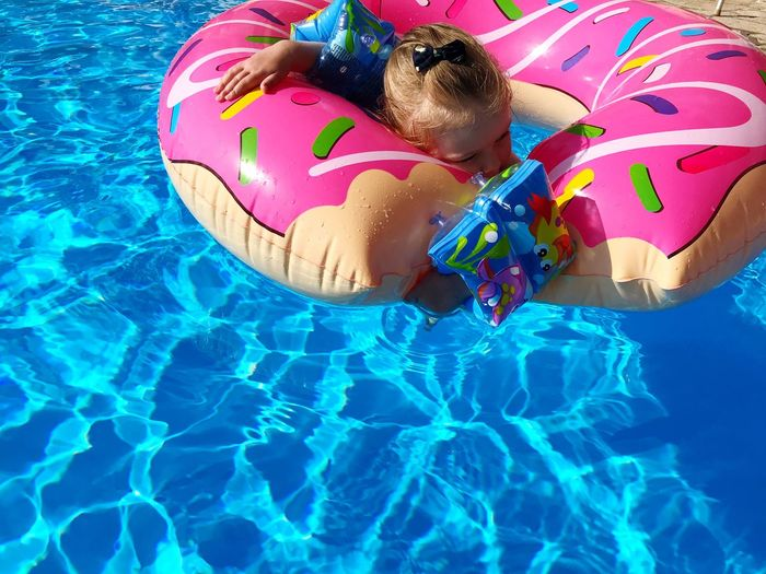High angle view of child floating in swimming pool