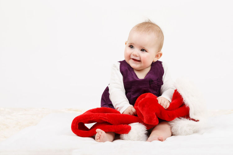 Cute baby girl lying on bed against white background